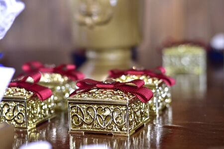 golden gift box with red bow on wooden table on blurred background