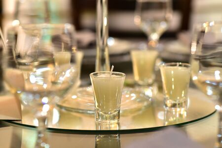 mirrored glass table with decorative candles on blurred background with noise