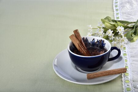 cinnamon tea cup with flower arrangement in the background on the table with green lining Zdjęcie Seryjne