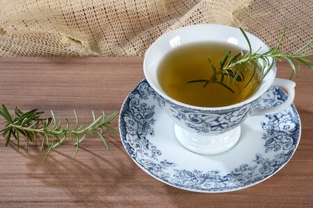 wooden table with cup of tea with branches of rosemary isolated on white background with space for text. Zdjęcie Seryjne