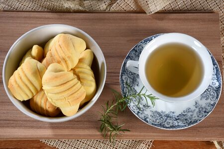 Brazilian snack on the table with cup of tea, cheese biscuit, vase with flowers on the gradient background with space for text.