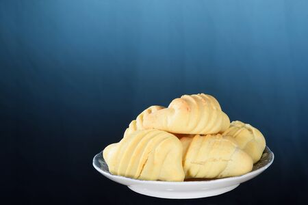 plate with typical Brazilian snack baked cheese cracker isolated on blue gradient background with space for text.
