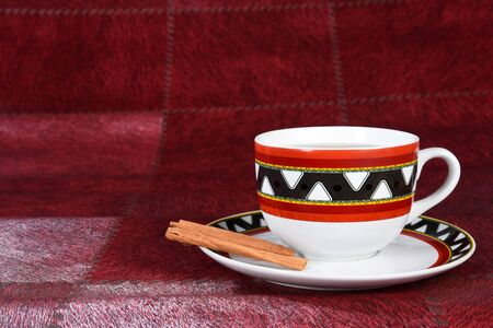 table with cup of tea with pieces of cinnamon isolated on red background with space for text