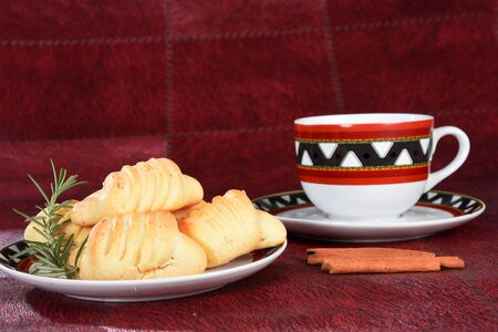 Brazilian snack on the table with cup of tea, cheese biscuit, vase with flowers on the gradient background with space for text