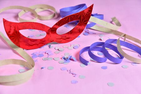 red carnival costume mask on colorful confetti necklace flowers and streamers with space for text.