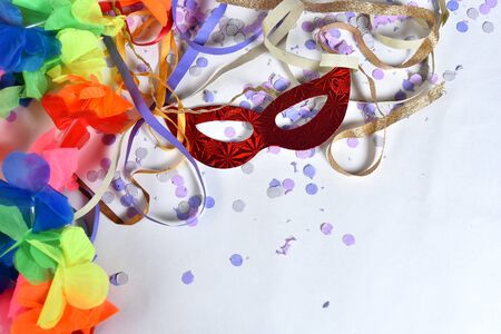 red carnival costume mask in colorful confetti and streamers on pink background with space for text,