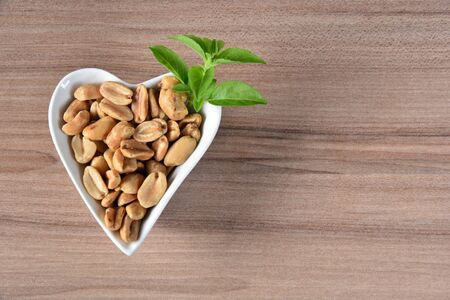 delicious and nutritious peanuts, peeled in a heart-shaped bowl with overhead view isolated on wooden table Reklamní fotografie
