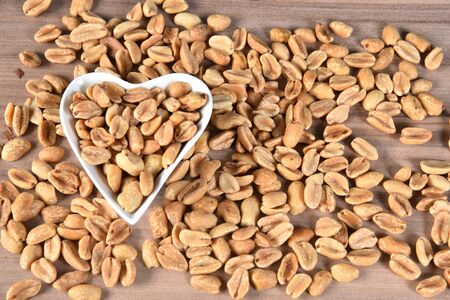 delicious and nutritious peanuts, peeled in a heart-shaped bowl with overhead view isolated on wooden table Zdjęcie Seryjne