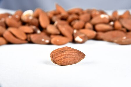 nutritious natural almonds scattered on the table in side view on white background with blurs