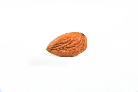 nutritious natural almonds scattered on the table in side view on white background with blurs.