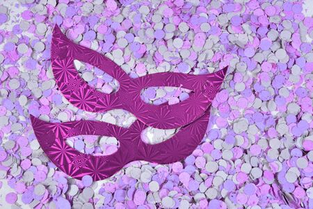 red brazilian carnival party costume mask on colorful confetti background with space for text,
