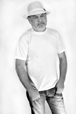 black and white photo of a man with a white beard in jeans, casual white shirt and hat on white background. Reklamní fotografie