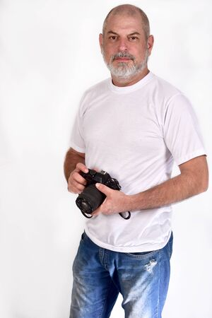 white-bearded man in white t-shirt jeans standing holding a photo camera on white background