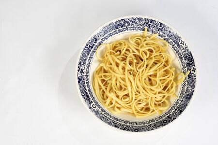 a plate of fresh spaghetti with olive oil on the white plate isolated over white background