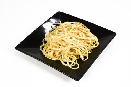 a plate of fresh spaghetti with olive oil on the black plate isolated over white background