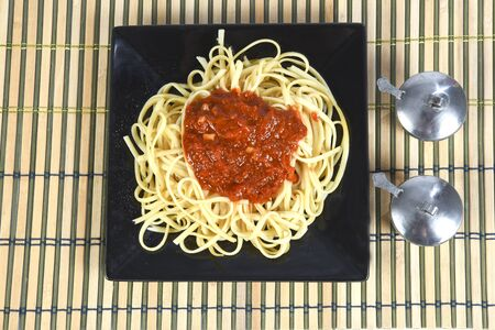 a plate of spaghetti with bolognese tomato sauce with olive oil on the black plate isolated over white background Reklamní fotografie