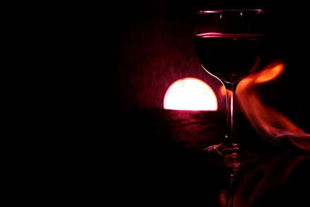 glass of red wine on glass table with fire around it on black background, romantic photo