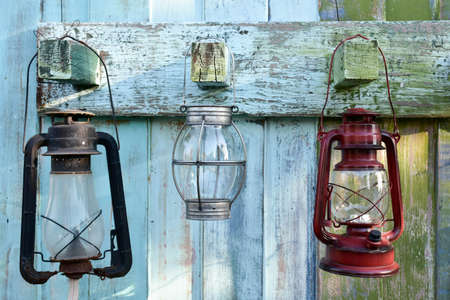 Old gas oil lamp. Hanging on old green and white wood. Stock Photo