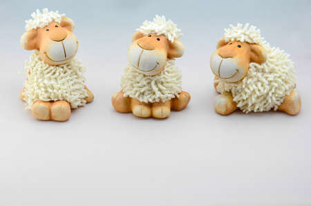 paschal lamb: three soft toys sheep at a grey backround