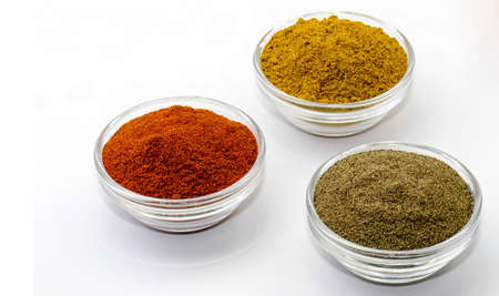 trituration: curry pepper and paprika in glass bowls isolated