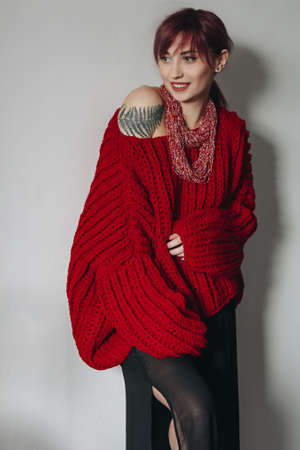 Portrait of young woman in stylish red oversized sweater and black skirt with tattoo on shoulder Stock Photo