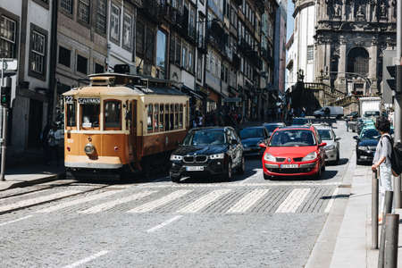 moderm: PORTO, PORTUGAL - APRIL, 30: Old tram and modern cars in the street of Porto, Portugal