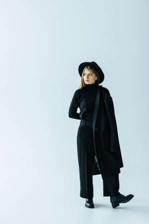 Young caucasian woman with black coat
