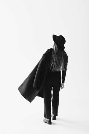 Young caucasian woman in black coat