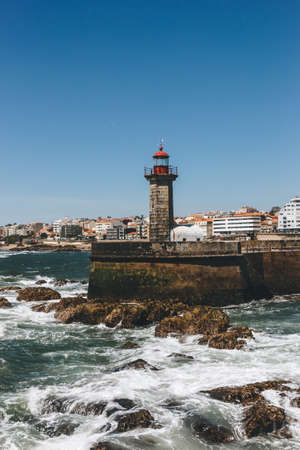 Old lighthouse and granite pier at the mouth of Douro river, Porto, Portugal