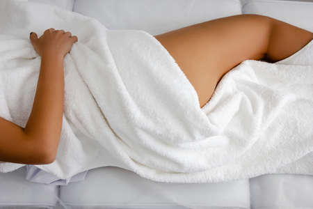 Sensual woman covers her naked body with towel. Beauty & Skin care concept.