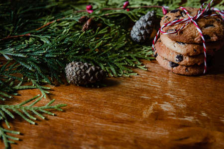 Christmas tree branch, bumps and cookies on wooden table