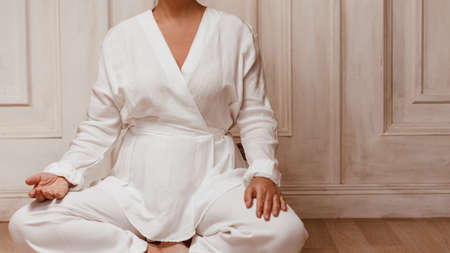 Practicing yoga an qigong at home. Unrecognizable woman wearing white costume sitting in meditation pose. Copy space Banque d'images