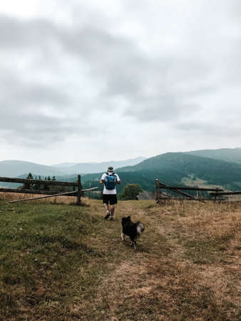 Man tourist with a dog walking through the valley in The Carpathians, Ukraine