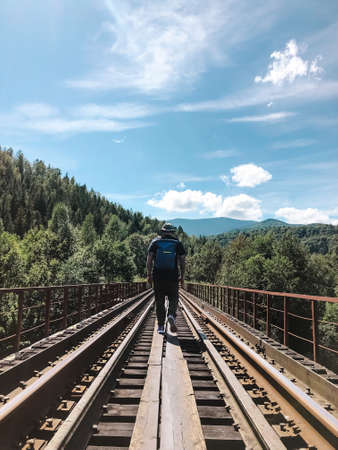 Man tourist with backpack walking through the railway bridge in The Carpathians, Ukraine