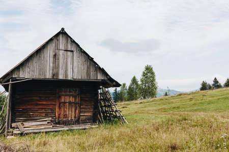Picturesque mountain landscape with old wooden house in the Carpathians Stock fotó