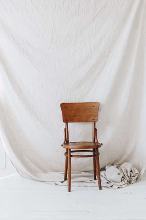 Old wooden chair on white textile background