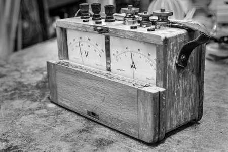electric meter: medidor eléctrico análogo de la vendimia en la antigua prueba de la tabla de madera