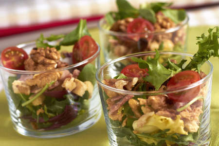 Fresh mixed salad with mixed greens, cherry tomatos and walnuts on crystal glasses