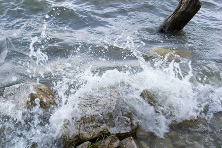 windstorm: Waves breaking rocks on the shore of the lake