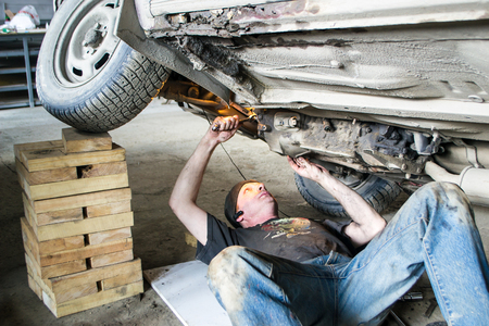 darn: A worker is repairing an old car. .