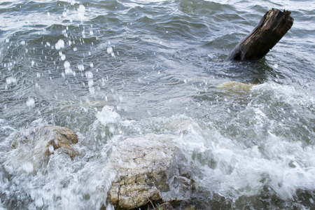 Waves breaking rocks on the shore of the lake