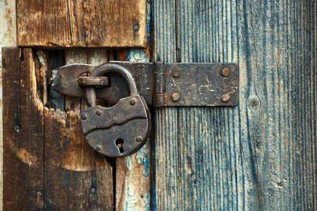 Old master lock pad locked on wooden door.