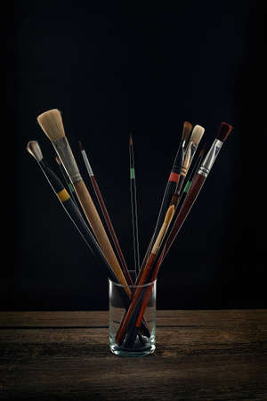 Paint brushes in a glass black background Stock Photo