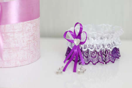 Wedding purple garter and flowers on a white table