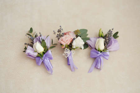 Stylish buttonhole, Boutonniere for the groom. Wedding accessory bridesmaid on the table standing on wooden background. flat lay. top view.