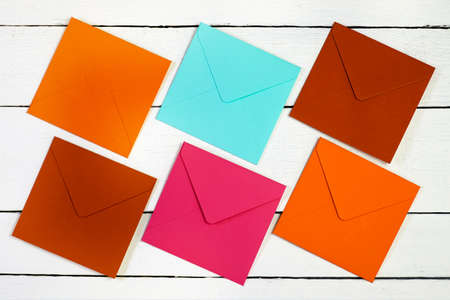 Top view image of multi-colored square envelopes on a white textured wooden table.