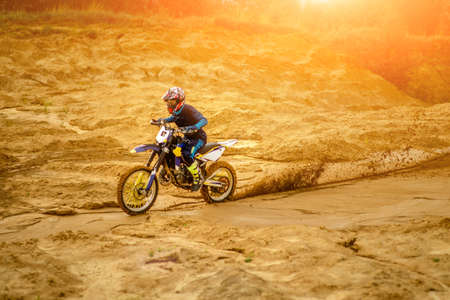 Professional Motorcycle Rider Driving on the desert and Further Down the Off-Road Track. It's Sunset and Track is Covered with Smoke Mist.
