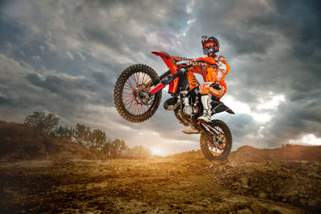 Side View of the Professional Motorcycle Rider Driving on the mountains and Further Down the Off-Road Track. Its Sunset and Track is Covered with Smoke Mist.