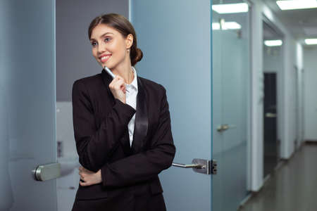 Young businesswoman standing waiting at an interior glass entrance door to the office. Copy space.