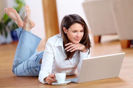 ノート パソコンと、床の上にコーヒーのカップを持つ若い女性